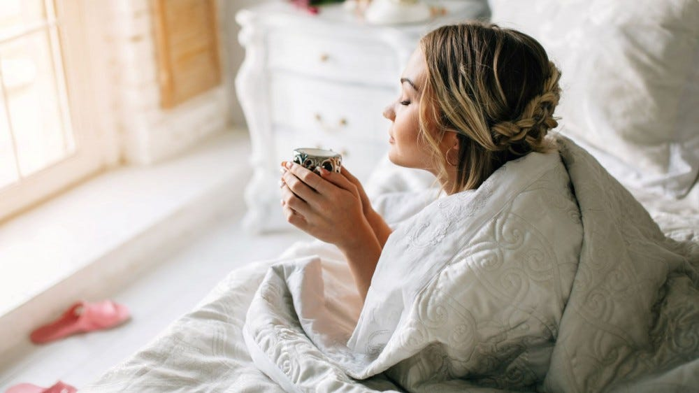 A woman drinking coffee in bed in the morning.