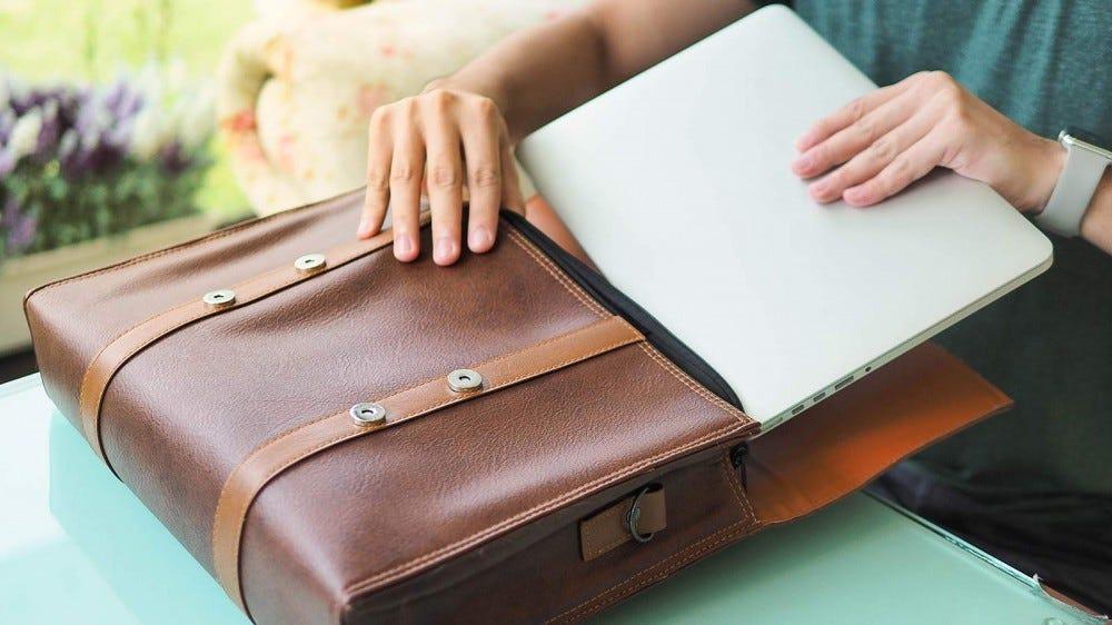 A person sliding a laptop into a bag.