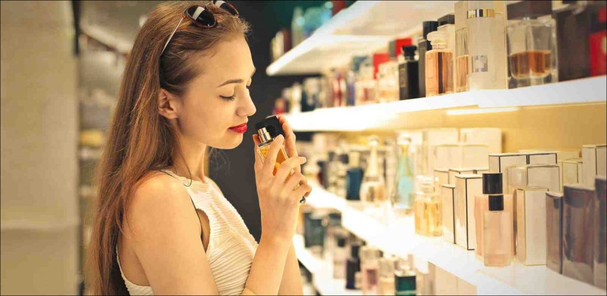 woman choosing from perfumes on a store shelf