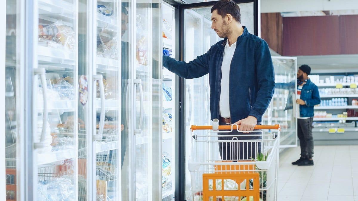 Man retrieving items from a grocery store freezer.