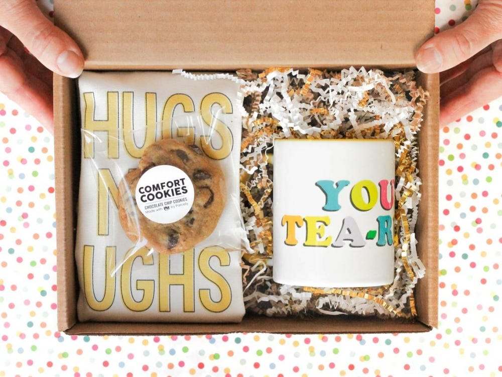 """A box filled with self-care goods features cookies, a mug, and a graphic that reads """"hugs not ughs."""""""