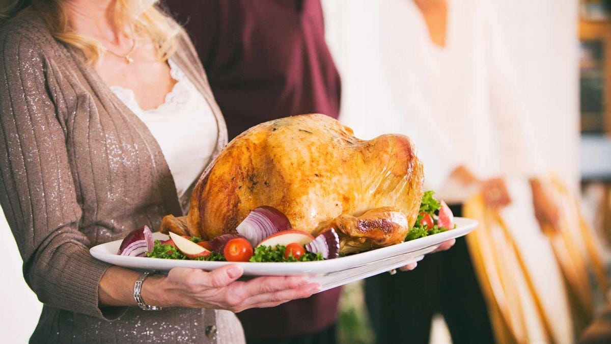 woman holding a platter with a large roasted turkey