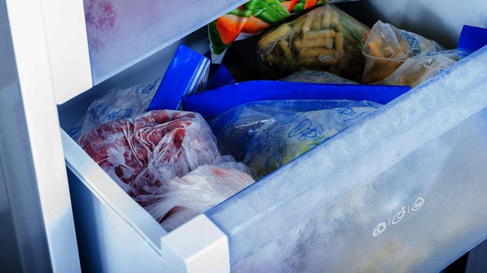 A bin full of frozen food in a freezer.