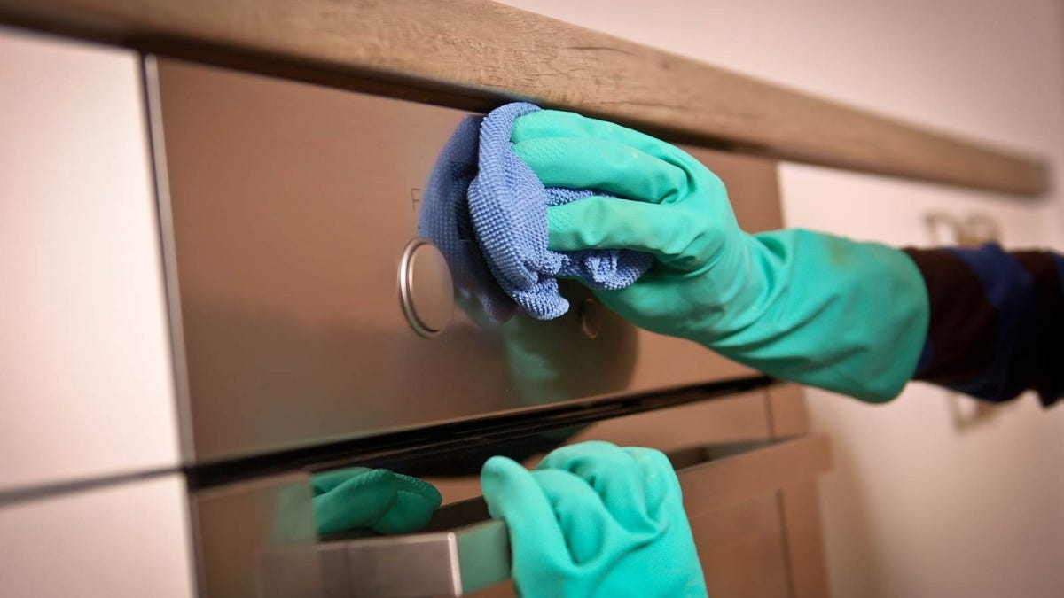 A pair of hands in rubber gloves wiping a stainless steel dishwasher with a sponge.