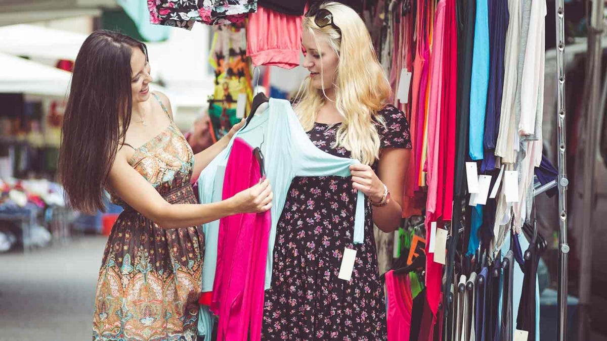 Two friends shopping for used clothes