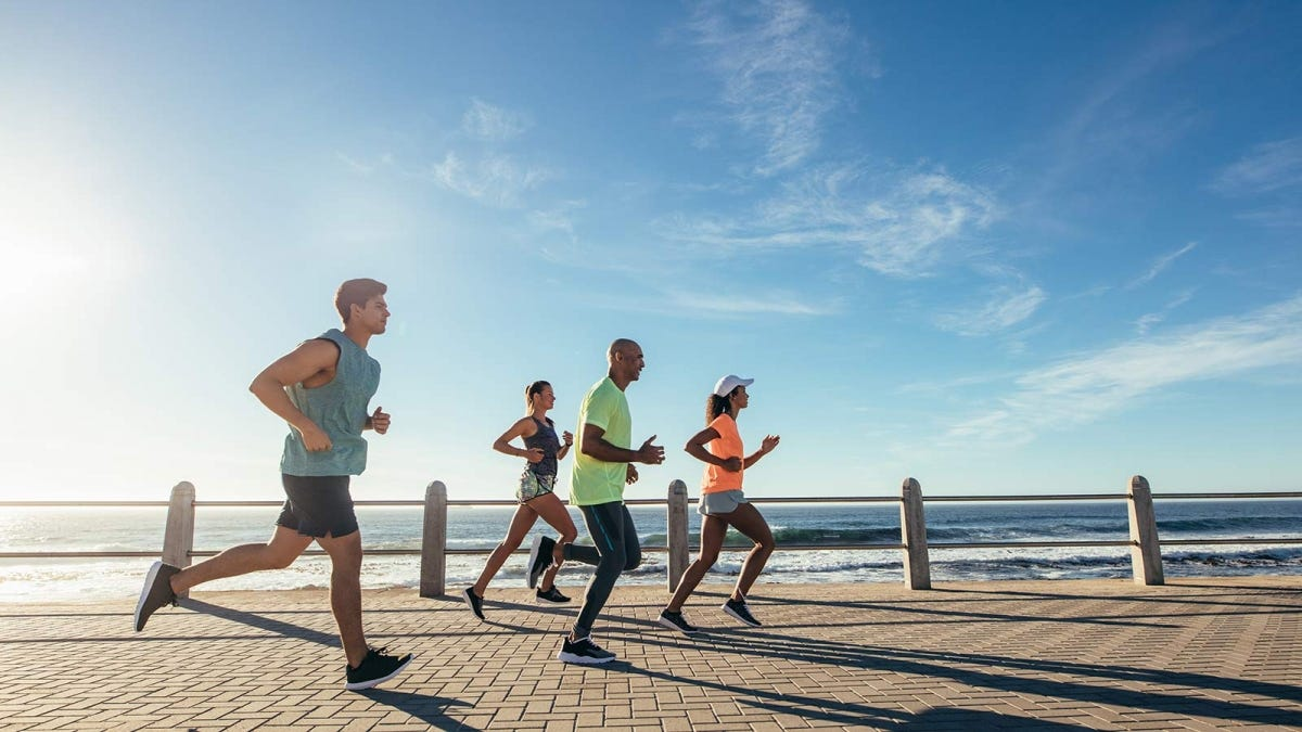 A group of people running down a brick path beside the ocean.