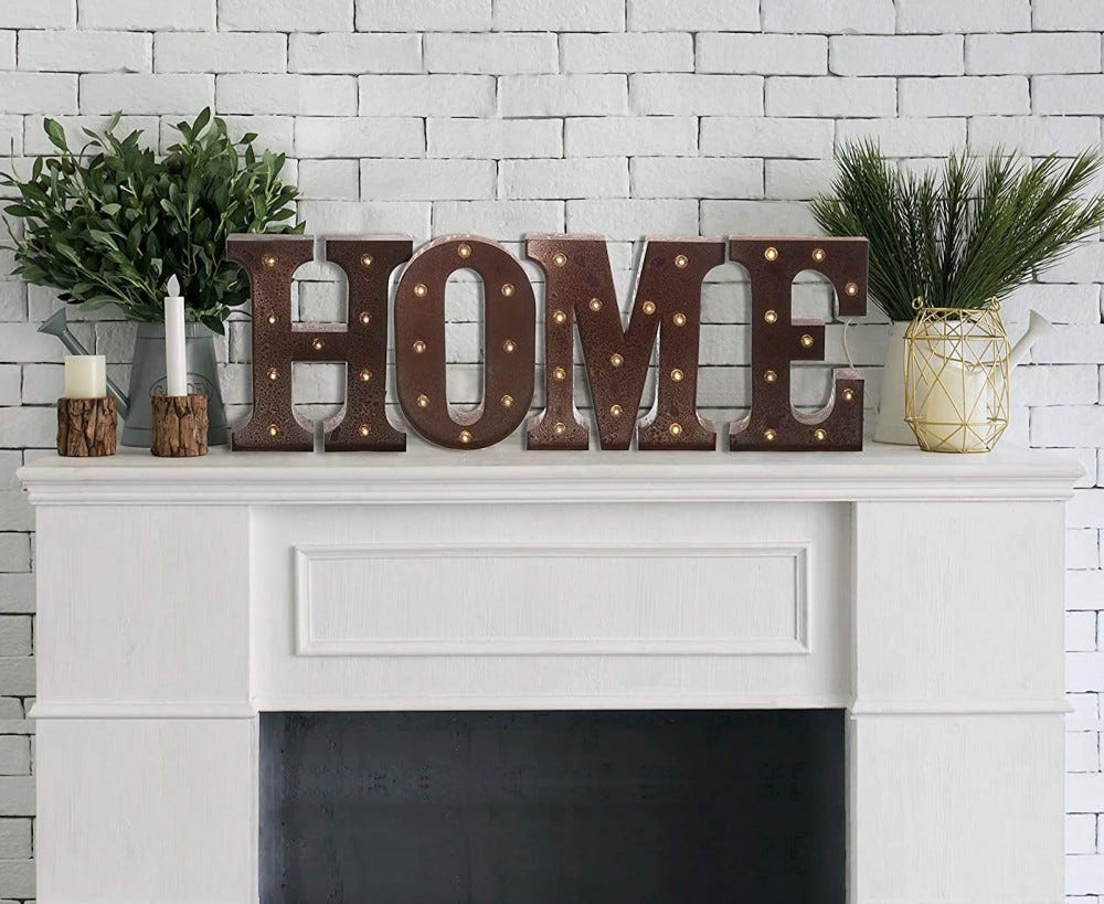 """Metal letters with lightbulbs spelling out """"HOME"""" atop a fireplace"""