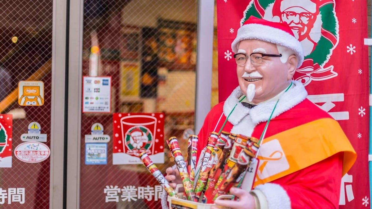 A Colonel Sanders statue in Santa garb outside of a Japanese KFC.