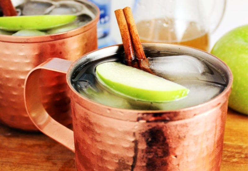 Two Moscow Mules in copper mugs, garnished with granny smith apple slices and cinnamon sticks.