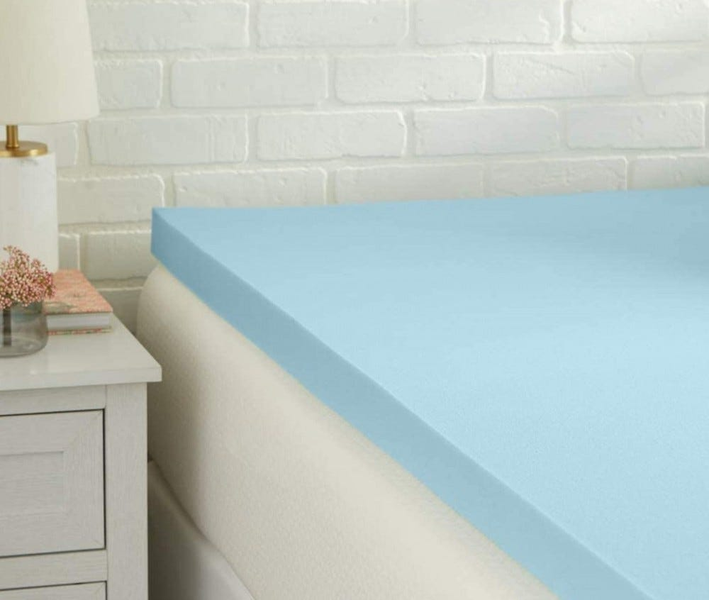 The corner of a blue foam mattress topper atop a white mattress