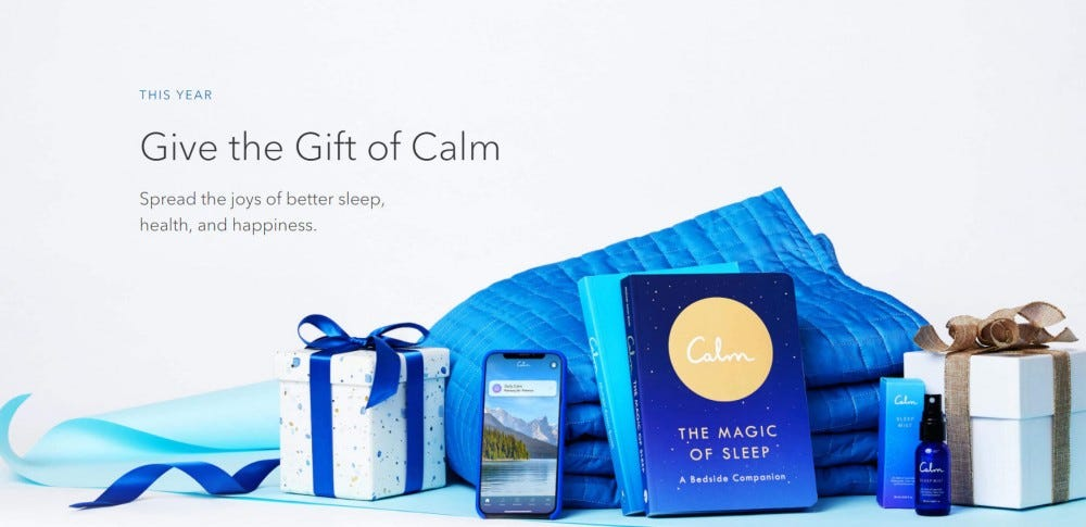"""An ad for the Calm gift subscription with the app open on a phone sitting next to a blanket, two presents, and """"The Magic of Sleep"""" book."""