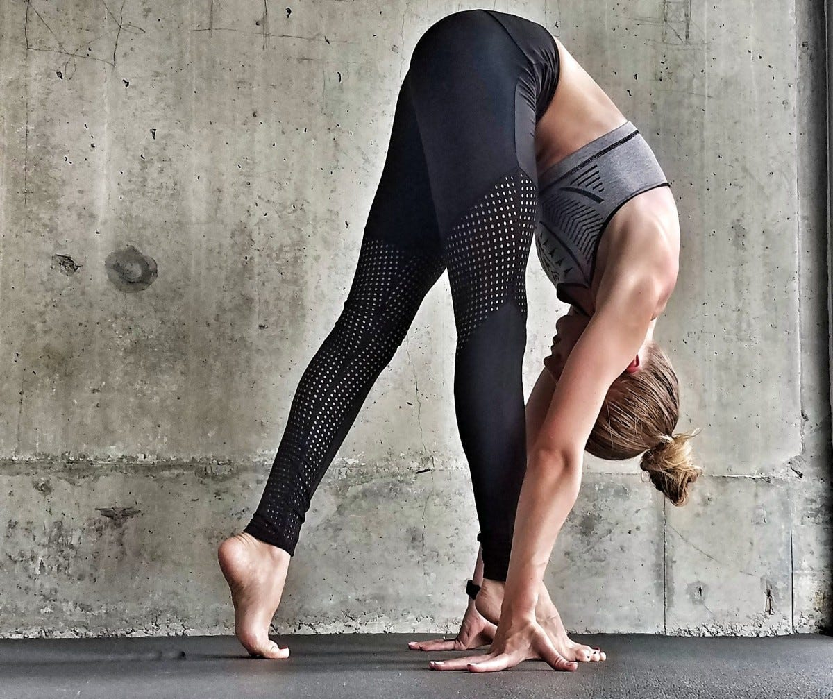 Woman doing a forward fold in front of a cement wall
