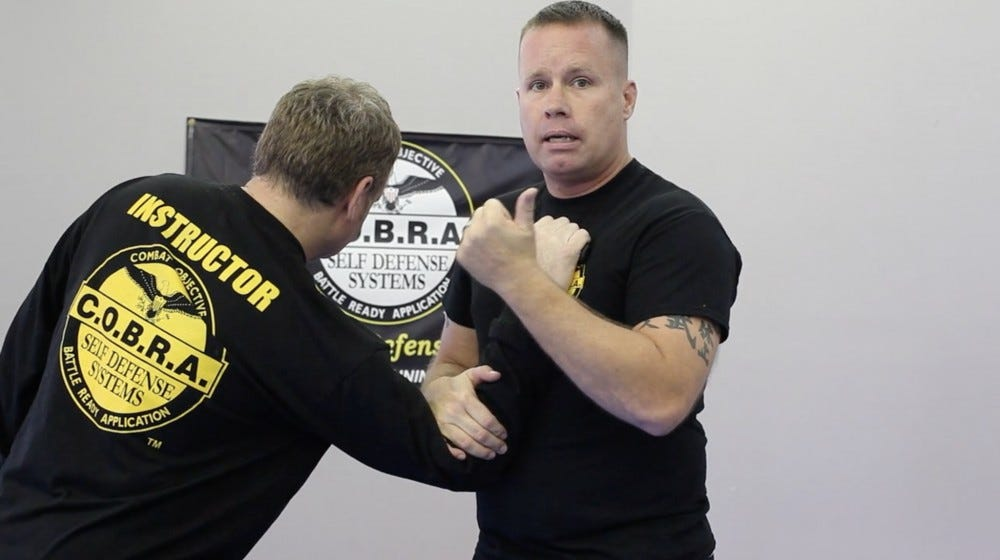 Two men demonstrating a self-defense move.
