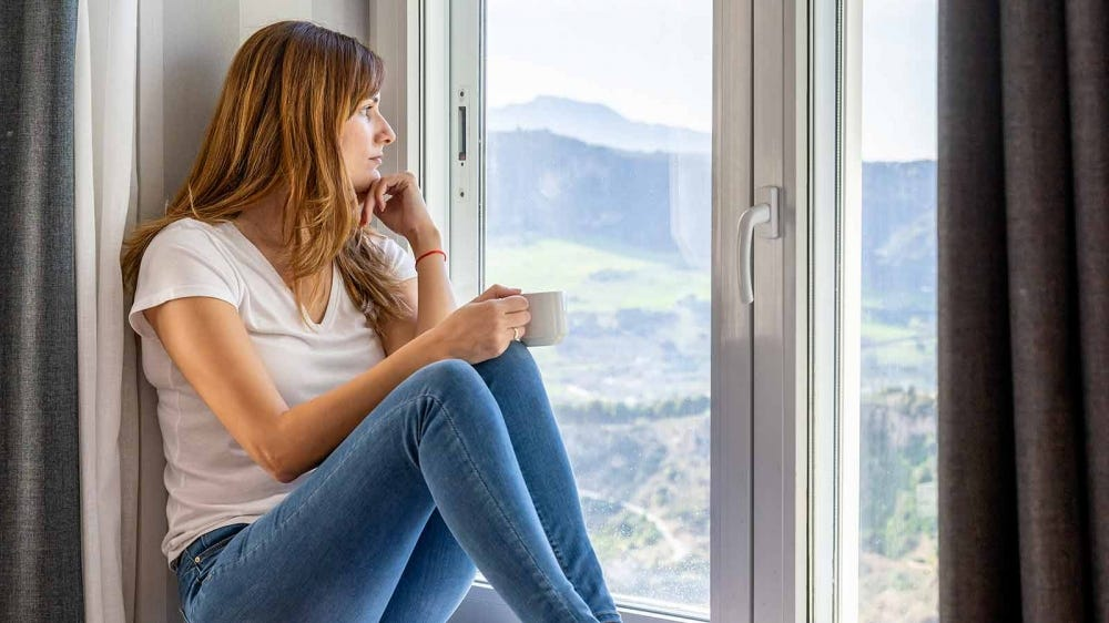 Woman looking out the window, drinking a cup of coffee.