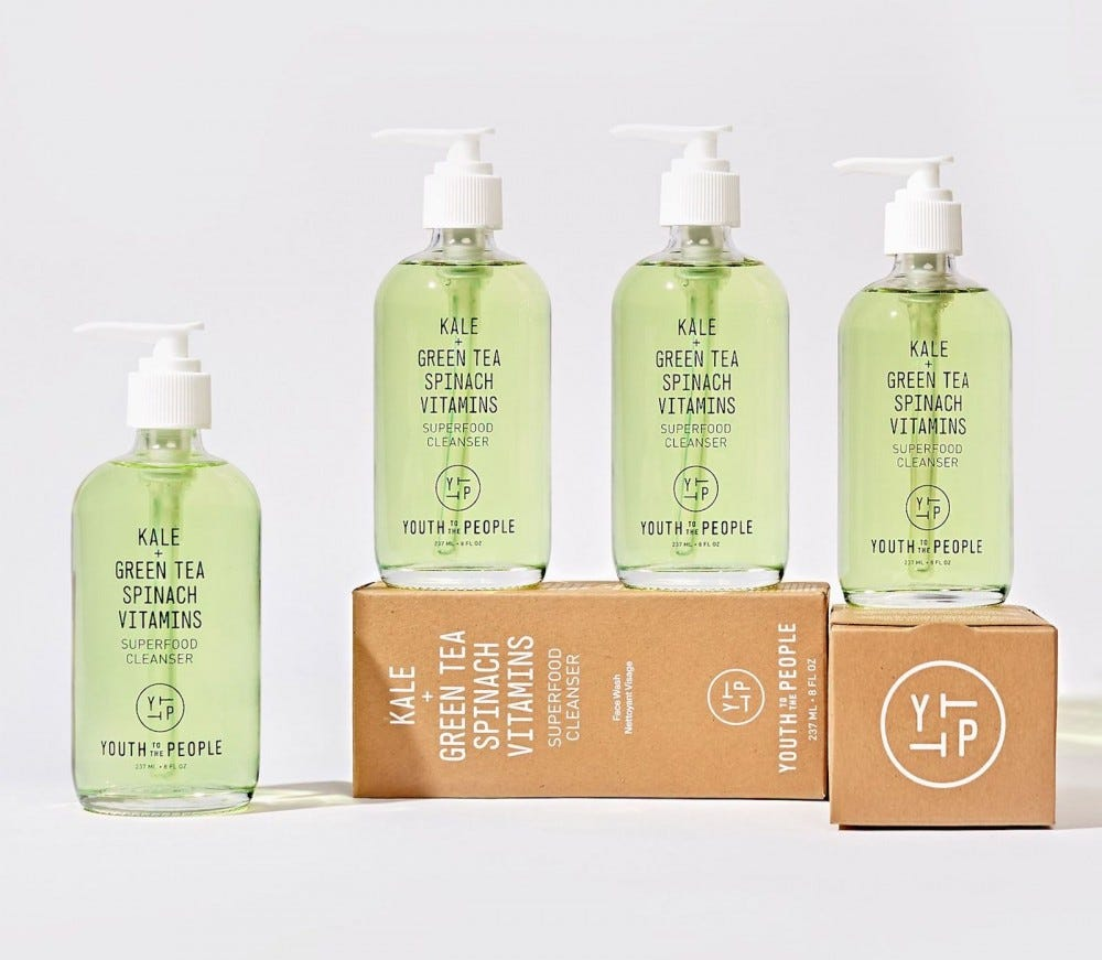Four bottles of pale green cleanser, three sitting on top of a brown box