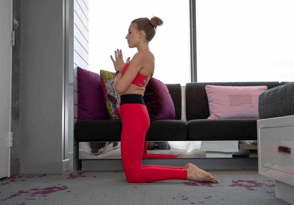 Woman doing yoga in her room wearing red clothes