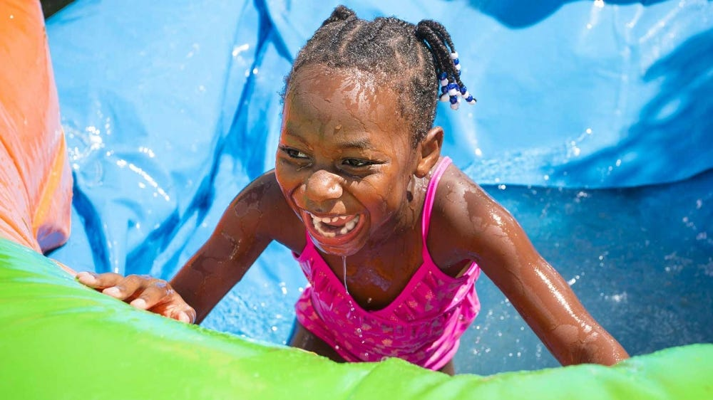 Young girl playing on a water slide.