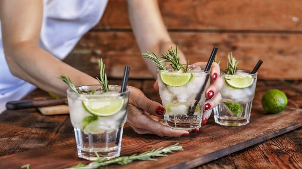A woman serving up gin and tonics with rosemary and lime.