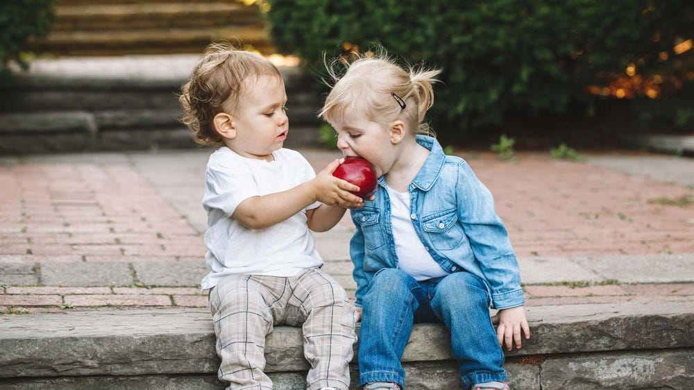 A toddler sharing an apple with his friend.