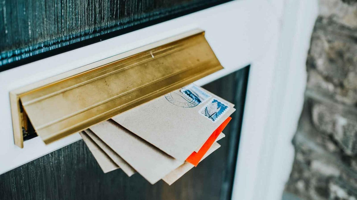 Postmarked mail, sticking out of a mail slot.