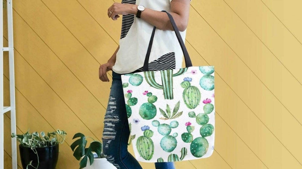A woman carrying a cactus-pattern tote bag over her arm.