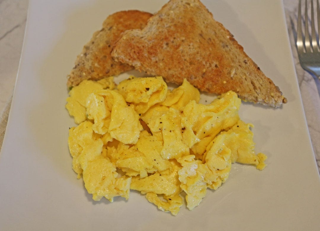 A plate of soft scrambled eggs with multigrain toast.
