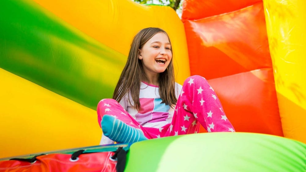 Girl playing in a colorful bounce house.