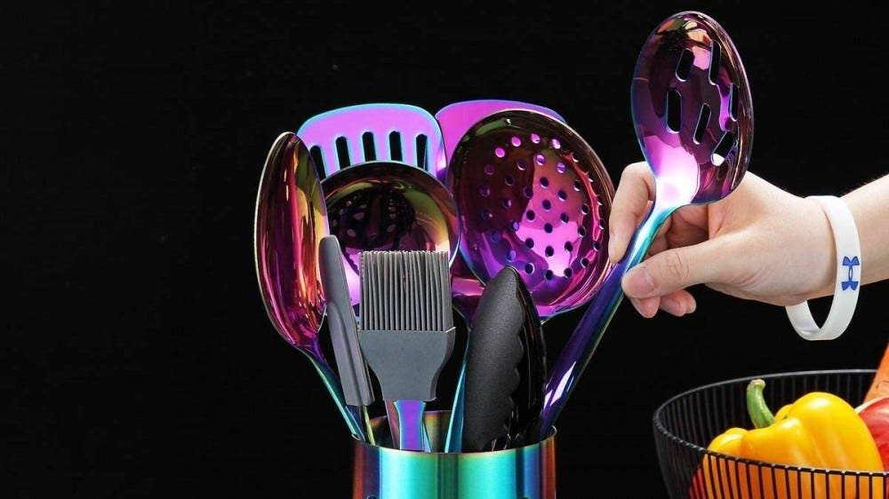 a set of rainbow holographic kitchen utensils sit inside a matching round container.