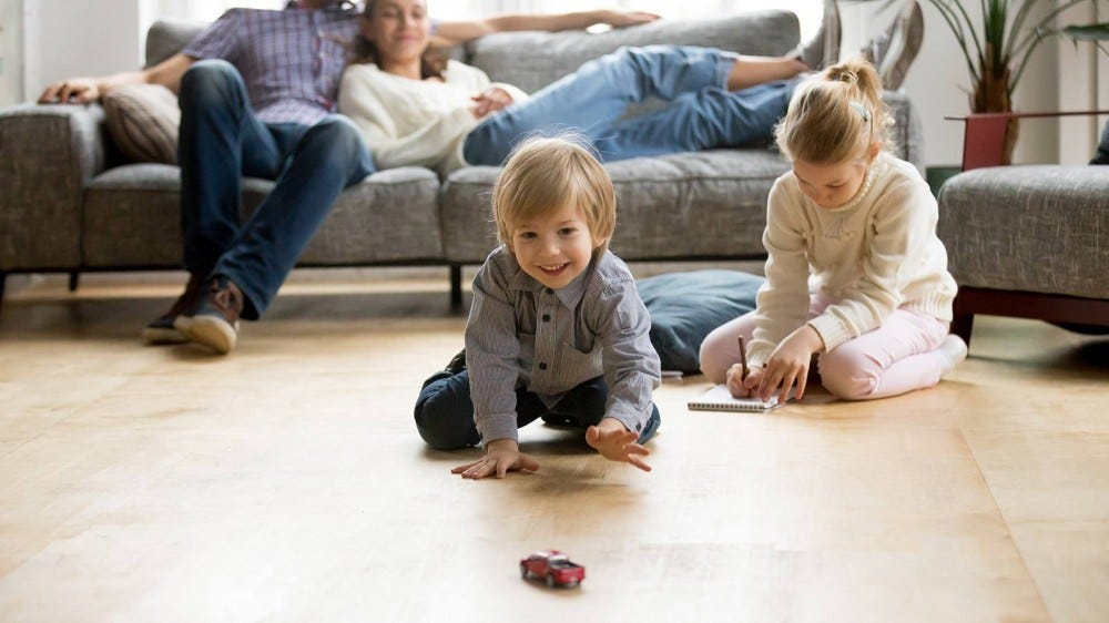 Parents sitting on the couch while their children play with toys in the living room.