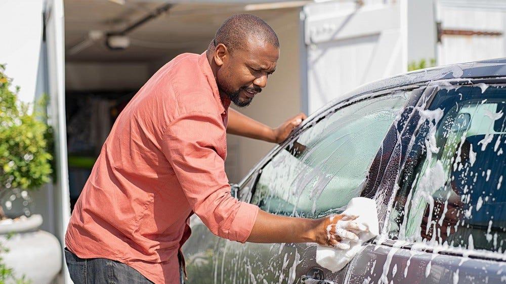 Man washing his car at home with a wash kit.