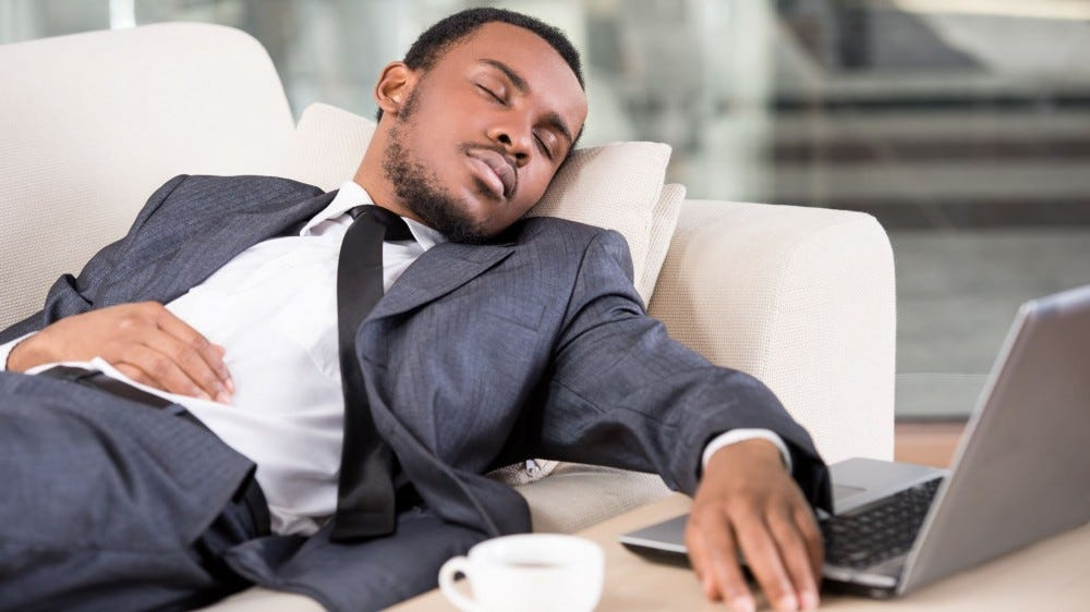 Man in a suit sleeping on an office couch next to an open laptop.