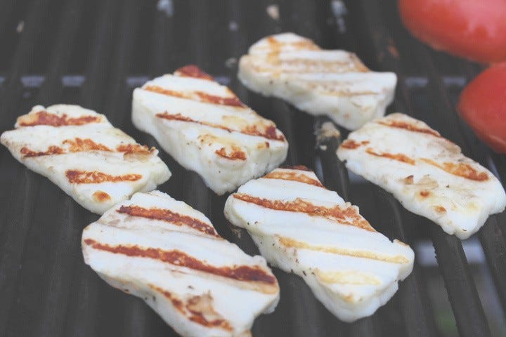 Six slices of halloumi cheese on a grill.