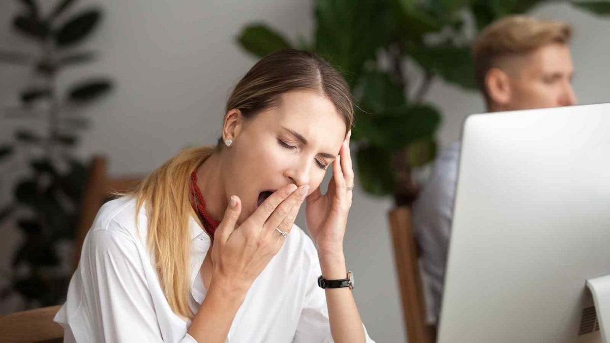 Woman yawning at the office, exhausted during the day.