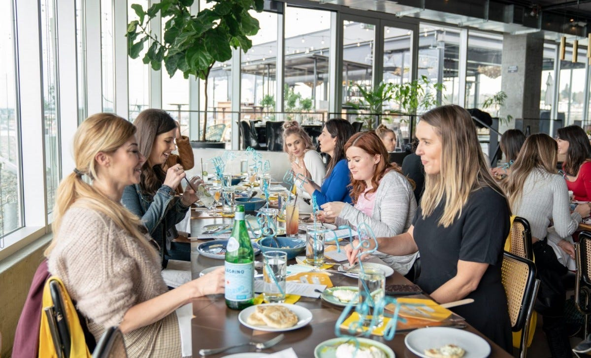 A group of women dining at a long table in a restaurant.