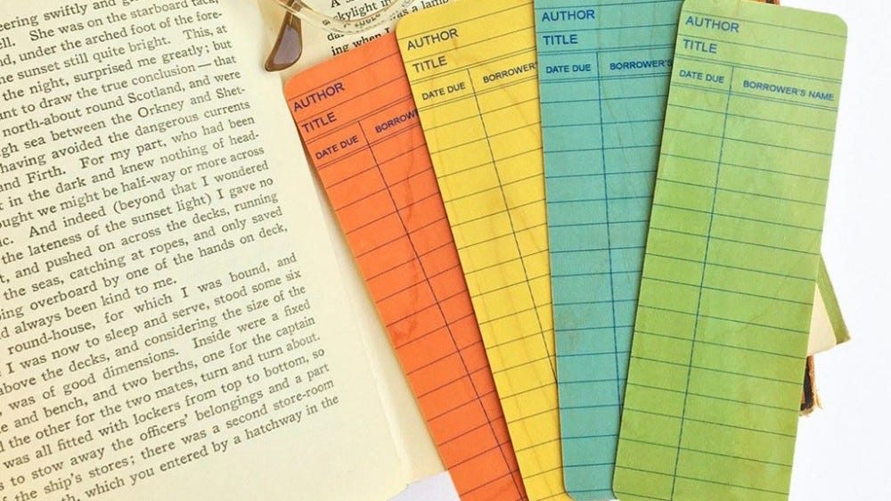 Wooden bookmarks printed to look like old library checkout cards.