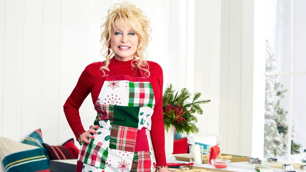 Dolly Parton in a brightly lit farmhouse-style kitchen, wearing a festive apron.