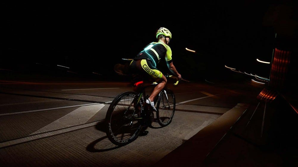 A cyclist wearing a Noxgear Tracer 360 safety vest at night.