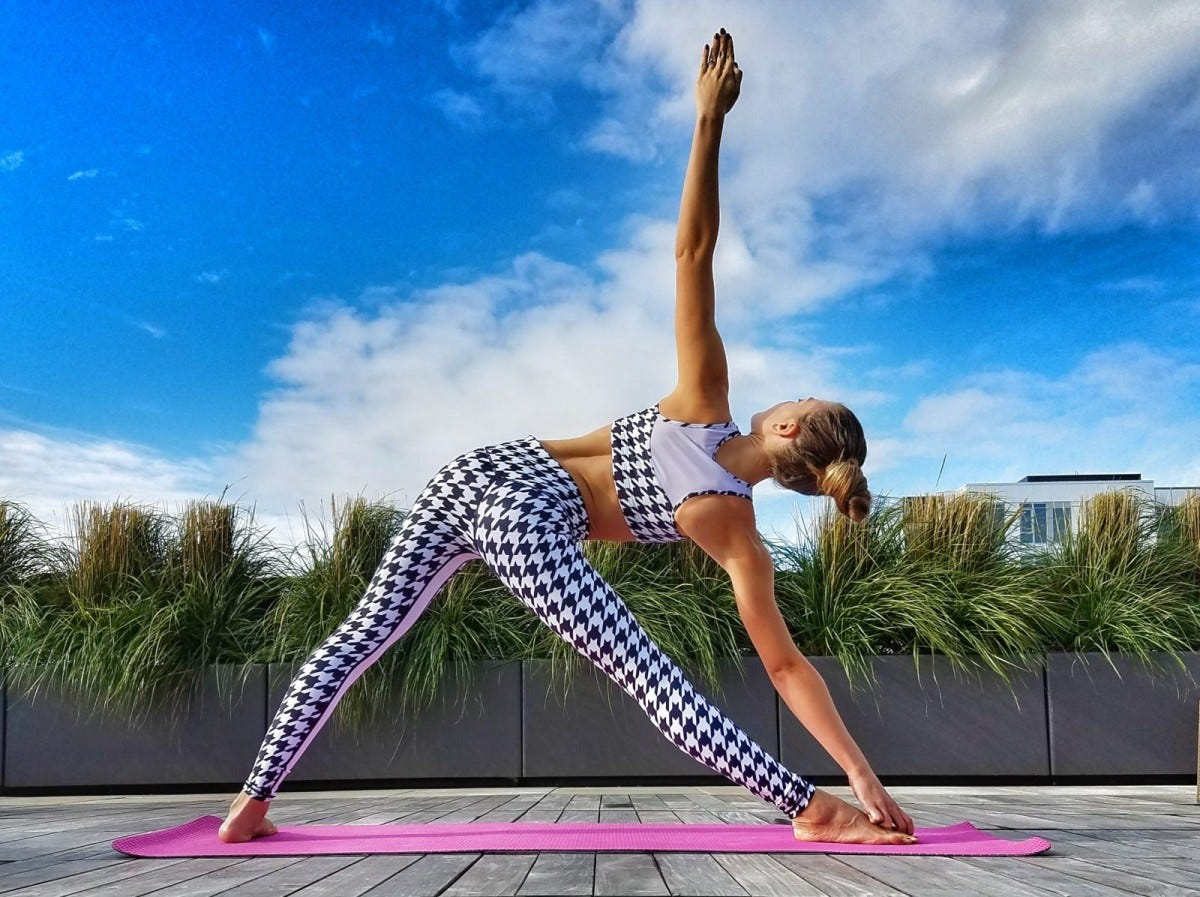 Woman doing triangle pose on a summer day