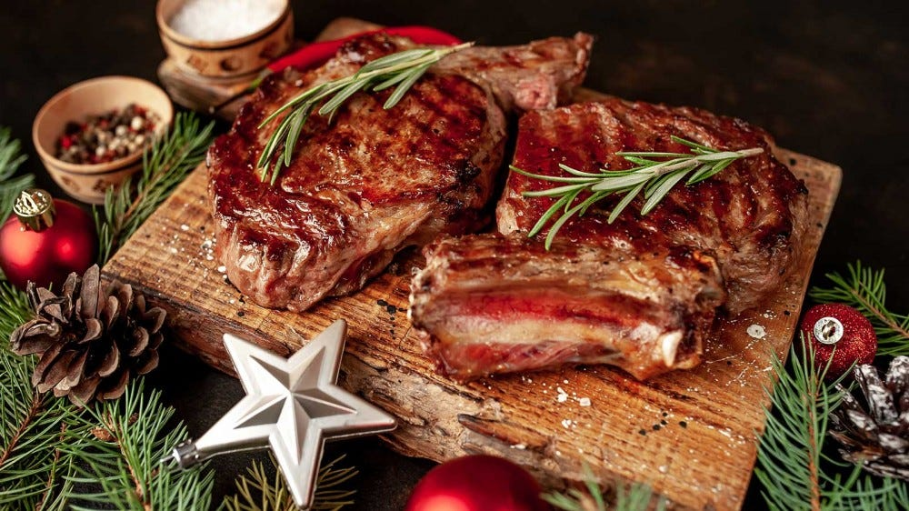 An oak grilling plank with two freshly grilled steaks resting on it, surrounded by holiday decorations.