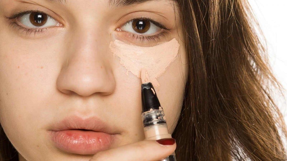 Woman applying concealer under her eyes.