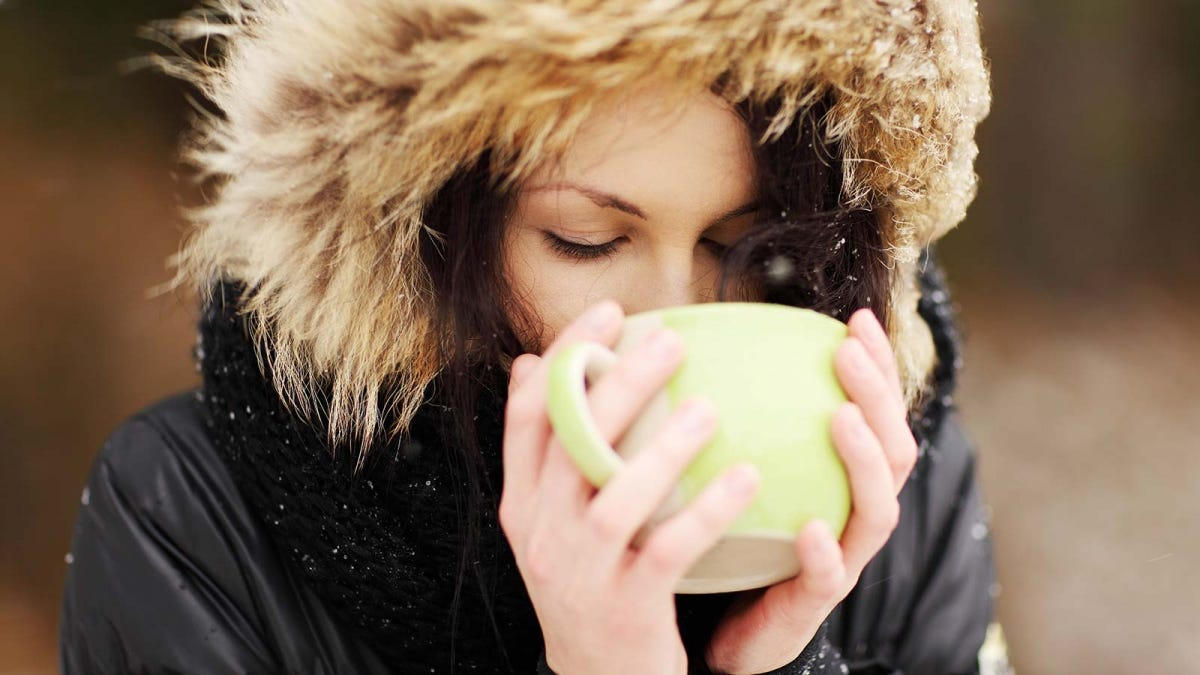 A woman in a fur-lined coat drinking out of a large mug.