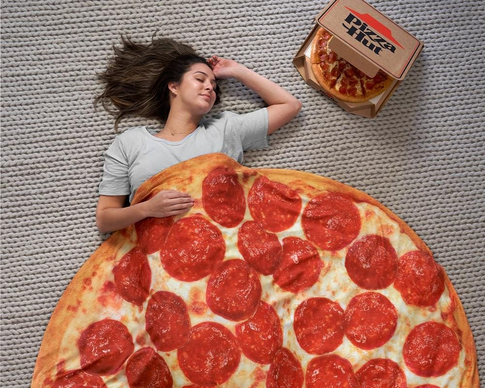 A woman lies on the floor covered in a pizza-patterned weighted blanket