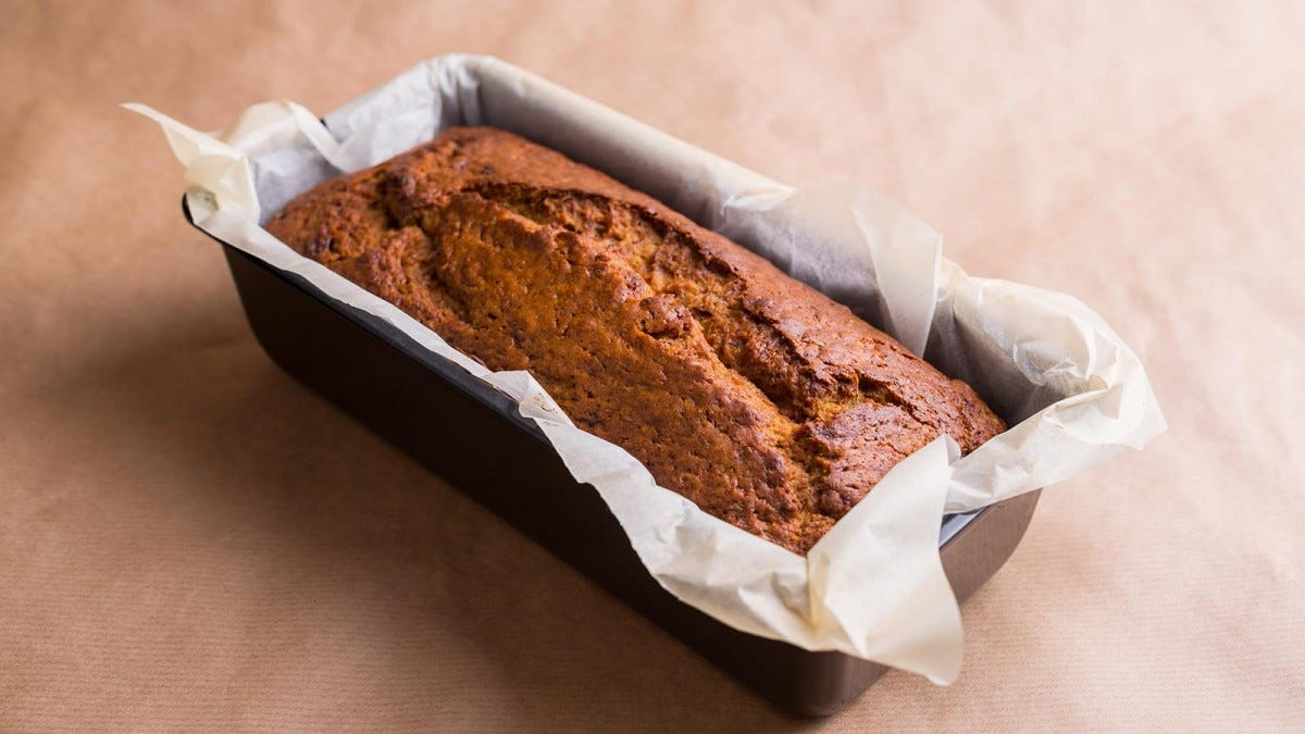 A loaf of banana bread in the pan, nestled among the parchment paper liner.