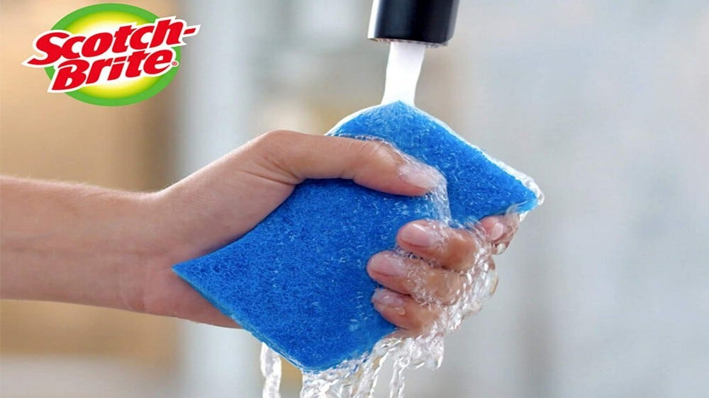 Someone with a fresh sponge under the tap, with the scotch-brite logo in the top left corner of the image.