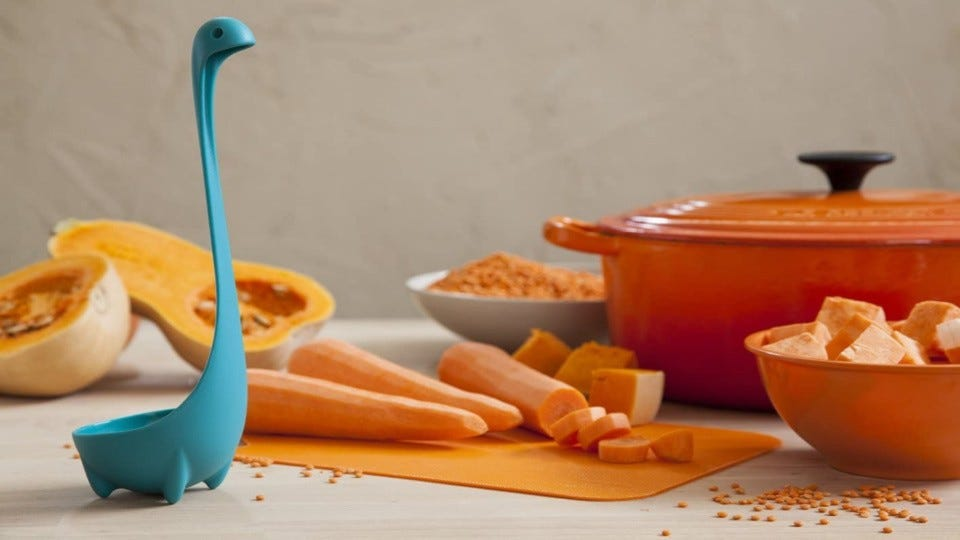 A blue Loch Ness Monster Ladle displayed with a bright orange dutch oven, prepped carrots and a halved butternut squash