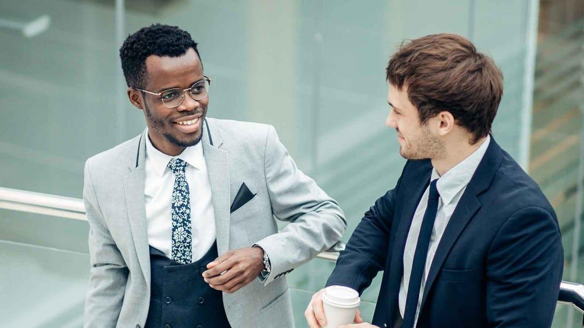two business men talking outside on a balcony