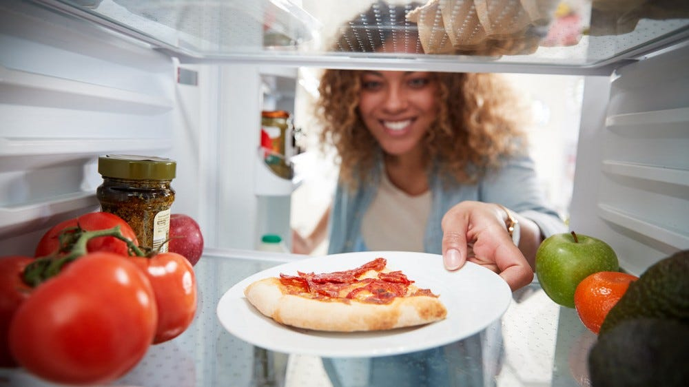 Woman getting left over pizza from her fridge to reheat.