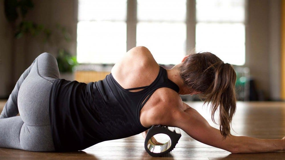 A woman using the deep-tissue TRX roller to dig into her muscles.