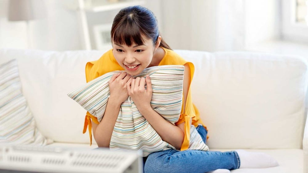 A woman sitting on a sofa and hugging a pillow while watching a rom-com.