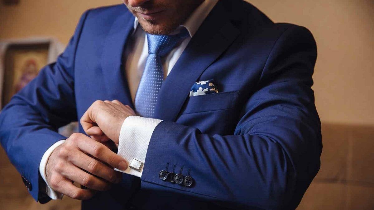 Man fastening a cufflink, dressed in lounge formal dress